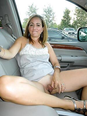 Elegant mature nude in motor vehicle